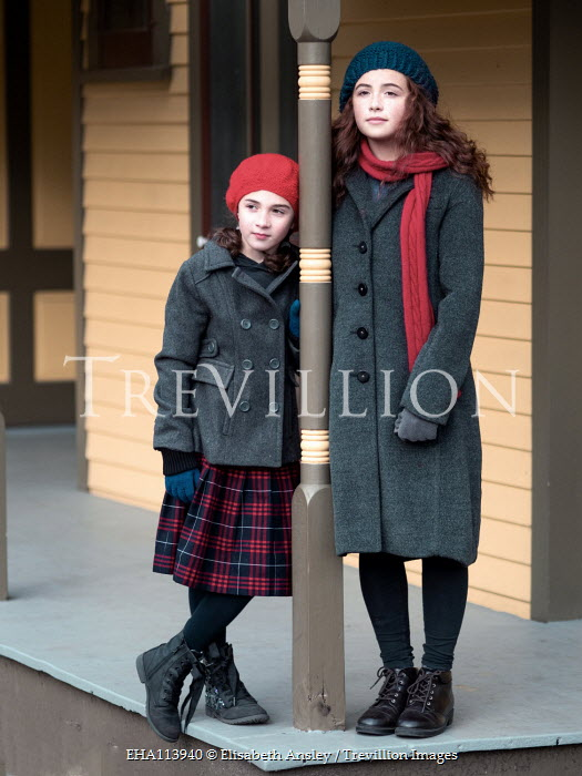 Elisabeth Ansley Sisters with woolly hats and coats on porch