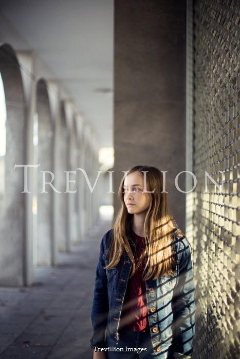 Kelly Sillaste Teenage girl by metal shutter gate