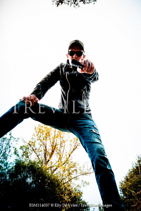Elly De Vries Low angle of man in baseball cap with pistol