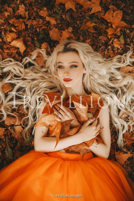 Jovana Rikalo Young woman in orange dress lying in autumn leaves