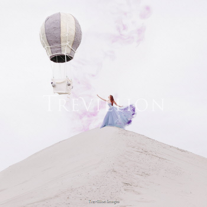 Jovana Rikalo Young woman on sand dune reaching for hot air balloon