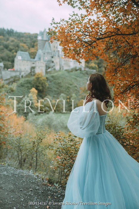 Jovana Rikalo Young woman in blue dress by castle