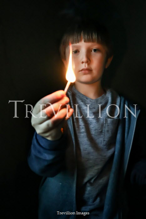 Stephen Carroll CLOSE UP OF BOY WITH MATCH ON FIRE AT NIGHT Children