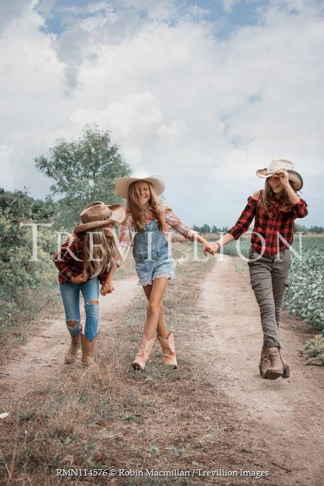 Robin Macmillan TEENAGE GIRLS IN COWBOY HATS IN COUNTRYSIDE Groups/Crowds