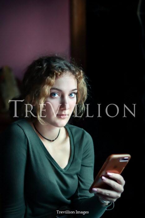 Stephen Carroll TEENAGE GIRL HOLDING MOBILE PHONE INDOORS Women