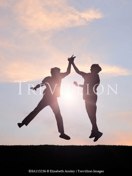 Elisabeth Ansley Silhouette of teenage boys doing high five at sunset