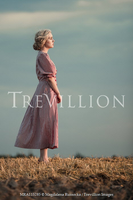 Magdalena Russocka retro woman in gingham dress standing in field