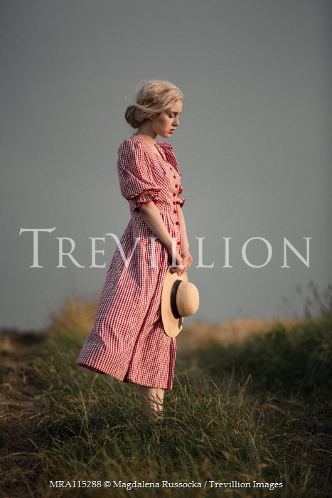 Magdalena Russocka retro woman in gingham dress holding hat standing in field