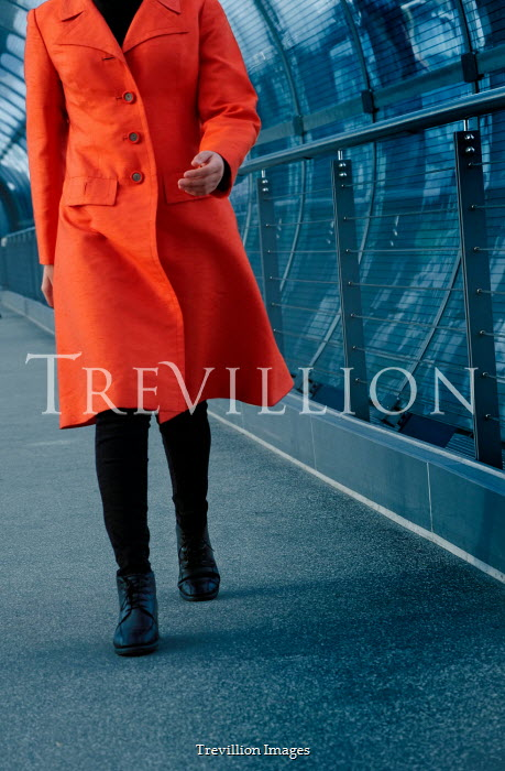 Ute Klaphake Woman in orange coat walking on pedestrian bridge