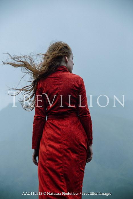 Natasza Fiedotjew Young redhead woman in red coat standing in rain