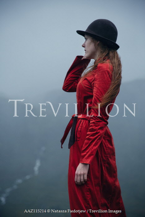 Natasza Fiedotjew Young redhead woman in red coat and hat looking at mountain valley in rain