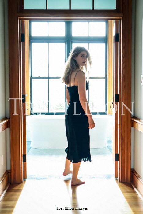Stephen Carroll Young woman in black dress standing in doorway to bathroom