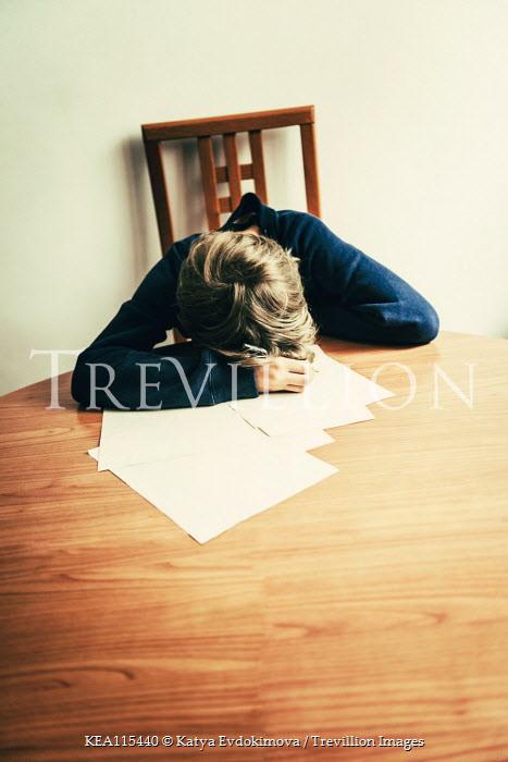 Katya Evdokimova Boy sleeping in pile of paper on table