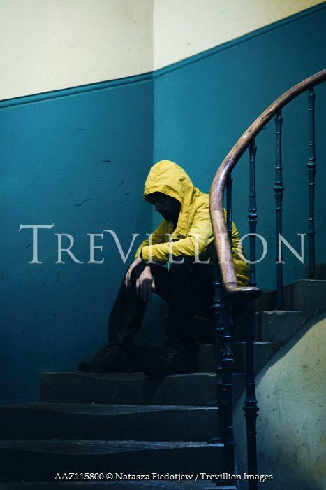 Natasza Fiedotjew Man in yellow rain coat sitting on stairs
