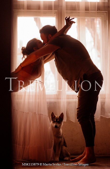 Marta Syrko Couple with dog kissing by window