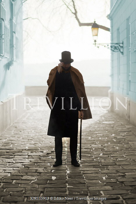 Ildiko Neer Man in top hat and cloak walking with cane on cobbled street