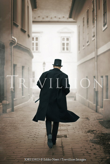 Ildiko Neer Man in top hat and cloak running on cobbled street