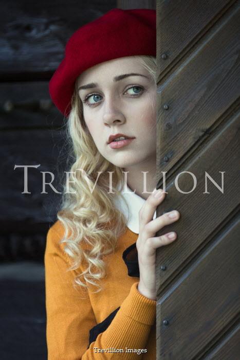 Magdalena Russocka Young woman in red beret behind wooden door