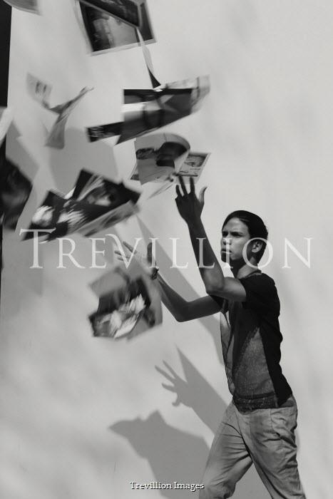 Giovan Battista D'Achille Young man throwing photographs