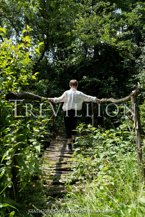 Galya Ivanova Boy walking on wooden bridge in forest