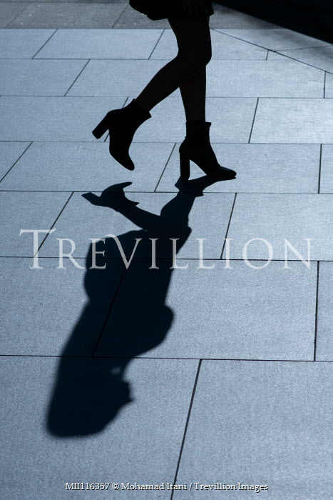 Mohamad Itani SILHOUETTED WOMAN AND SHADOW WALKING ON PAVEMENT Women