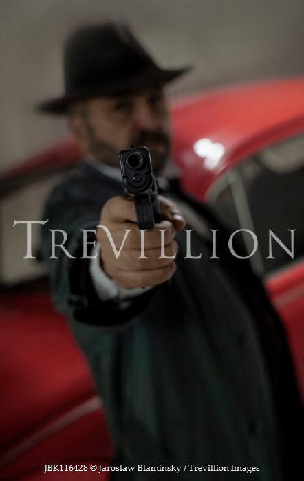Jaroslaw Blaminsky MAN IN HAT POINTING GUN BY RED CAR Men