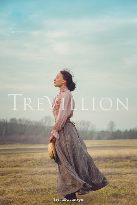 Joanna Czogala Victorian woman with straw hat standing in field