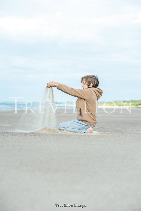 Katya Evdokimova Boy playing with sand on beach