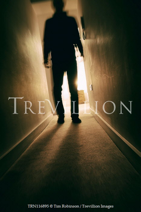 Tim Robinson Silhouette of man walking in corridor