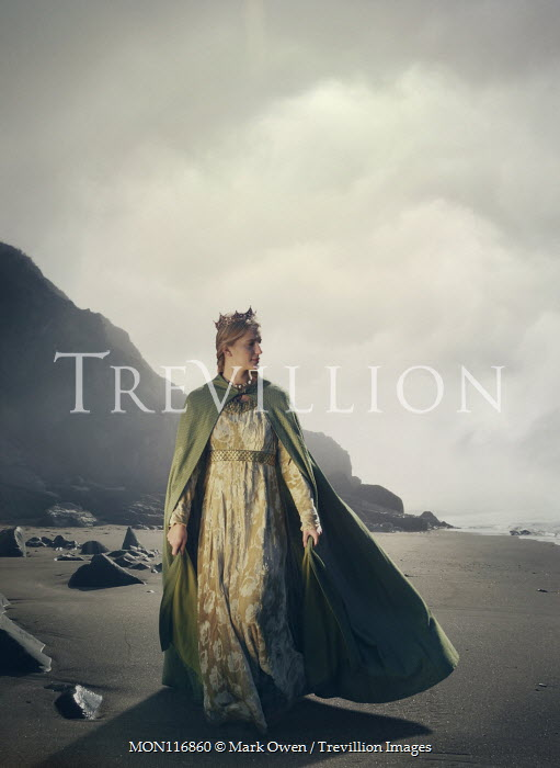 Mark Owen Young woman in medieval cloak walking on beach