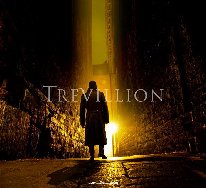 Stephen Mulcahey A silhouette of a man walking down a narrow alleyway