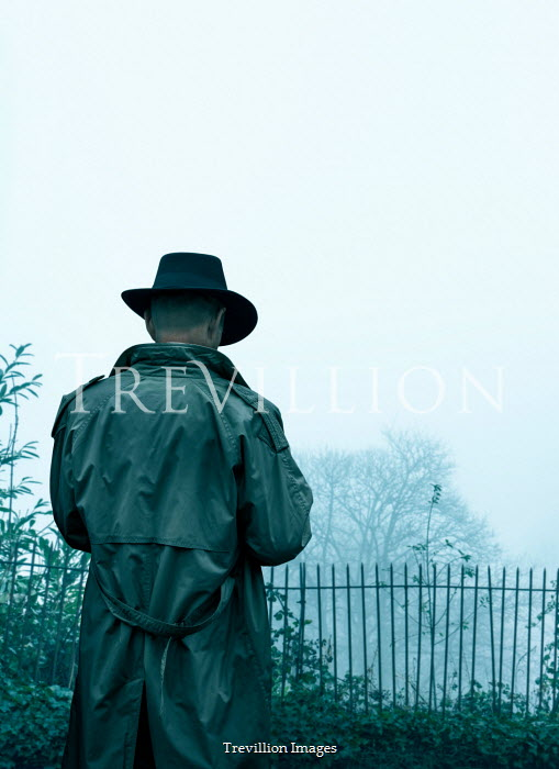Stephen Mulcahey a man in a trilby, waiting by  railings