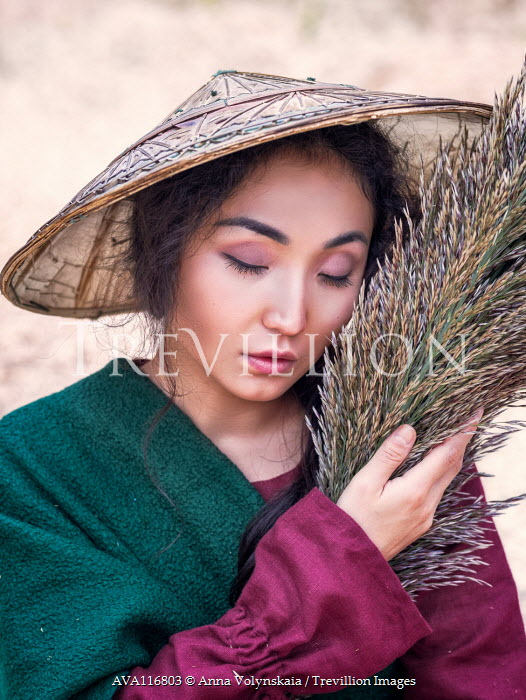 Anna Volynskaia Young woman in conical hat holding bundle of pampas grass