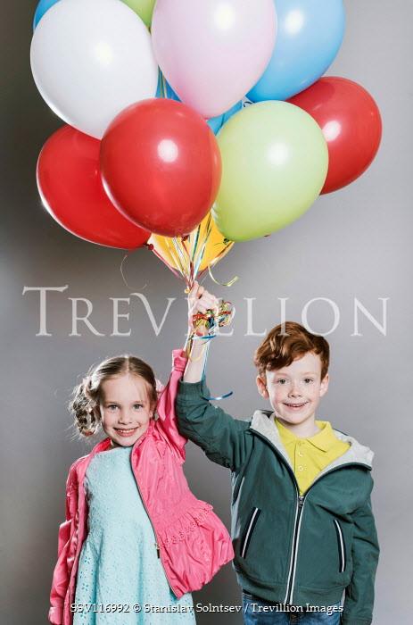 Stanislav Solntsev LITTLE GIRL AND BOY HOLDING BUNCH OF BALLOONS Children