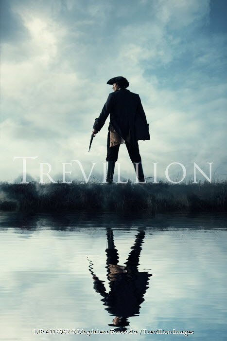 Magdalena Russocka historical man in tricorn hat and long jacket with flintlock standing by water