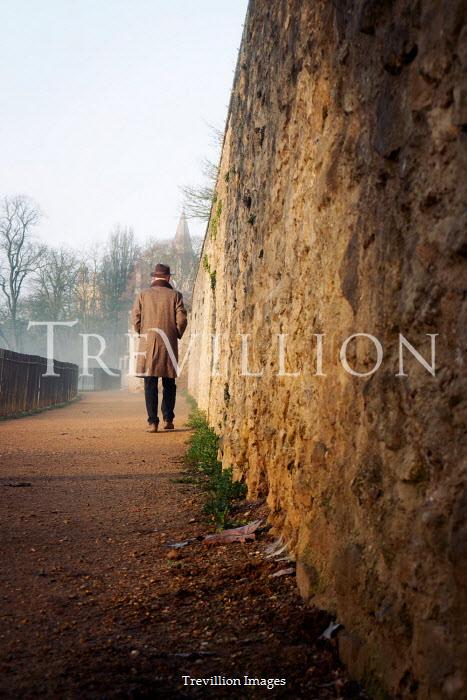 Tim Robinson MAN IN HAT WALKING BY WALL IN WINTER Men