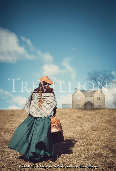 Magdalena Russocka historical woman with travel bag walking towards cottage house