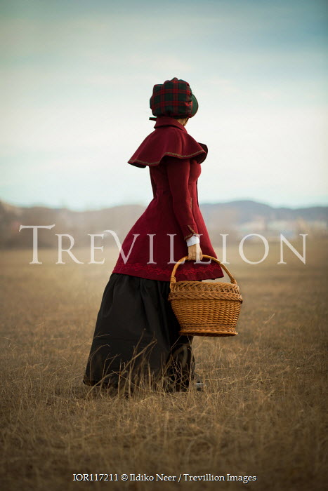 Ildiko Neer Historical woman standing in countryside with basket