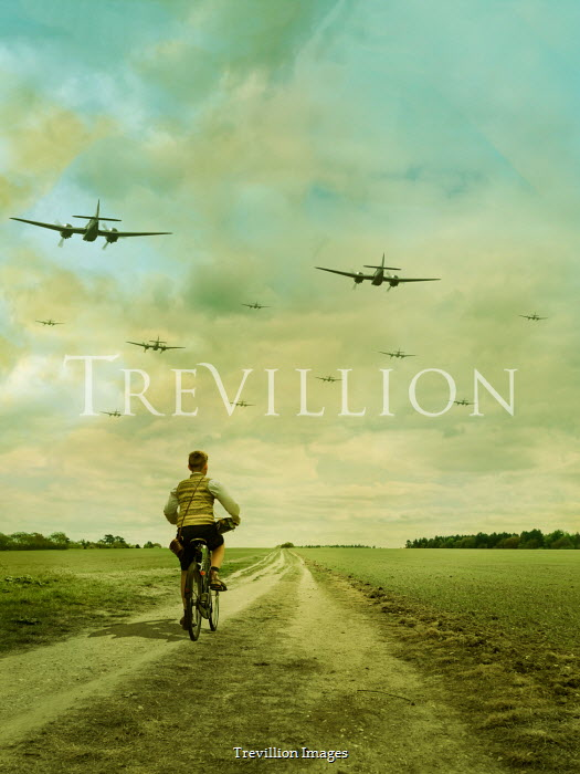 Stephen Mulcahey A ww2  boy riding a bike whilst bomber fly overhead