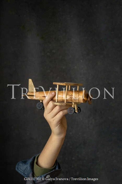 Galya Ivanova YOUNG MALE HAND HOLDING WOODEN TOY AEROPLANE Children