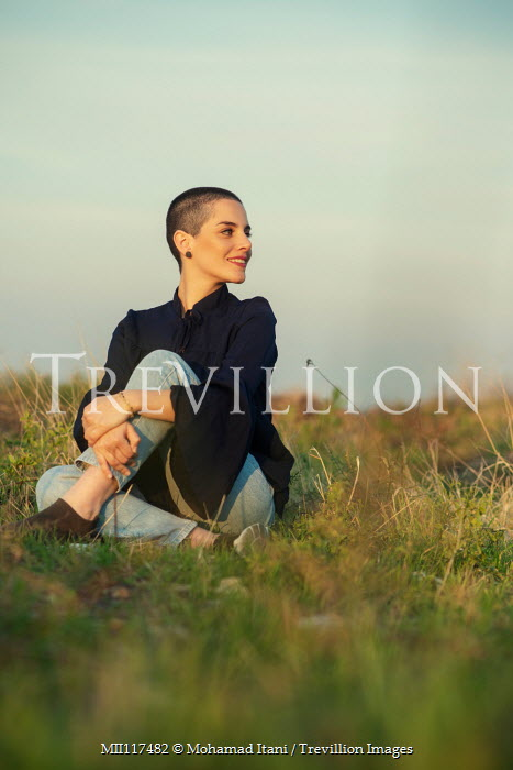 Mohamad Itani WOMAN WITH SHAVED HEAD SITTING IN FIELD Women