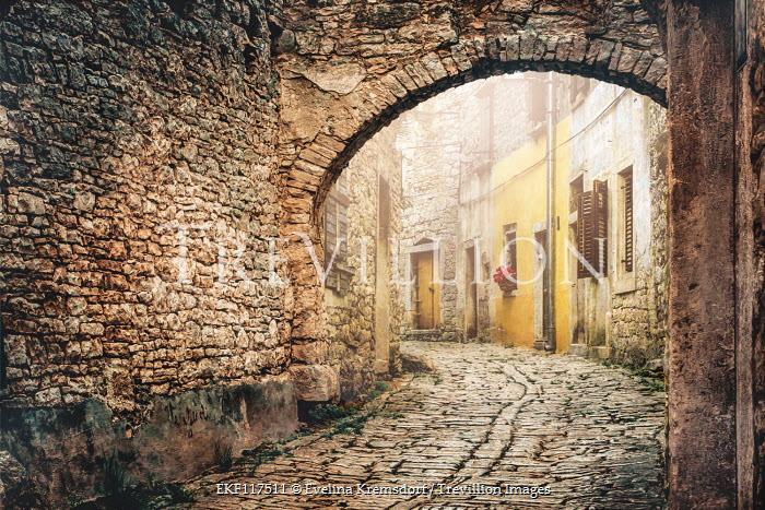 Evelina Kremsdorf Stone archway above cobblestone street in Italy