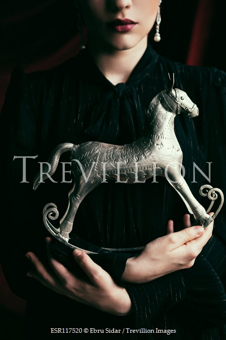 Ebru Sidar Young woman holding rocking horse ornament