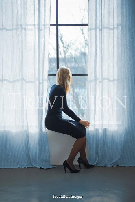 Ildiko Neer Modern woman sitting on window sill