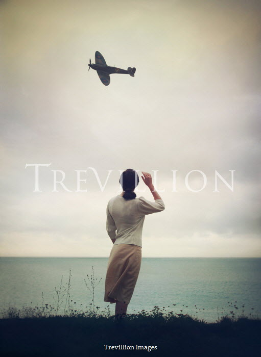 Mark Owen Woman in vintage sweater watching WWII fighter plane flying over sea
