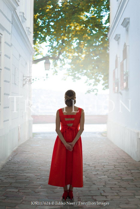 Ildiko Neer Woman in evening gown standing on cobbled street