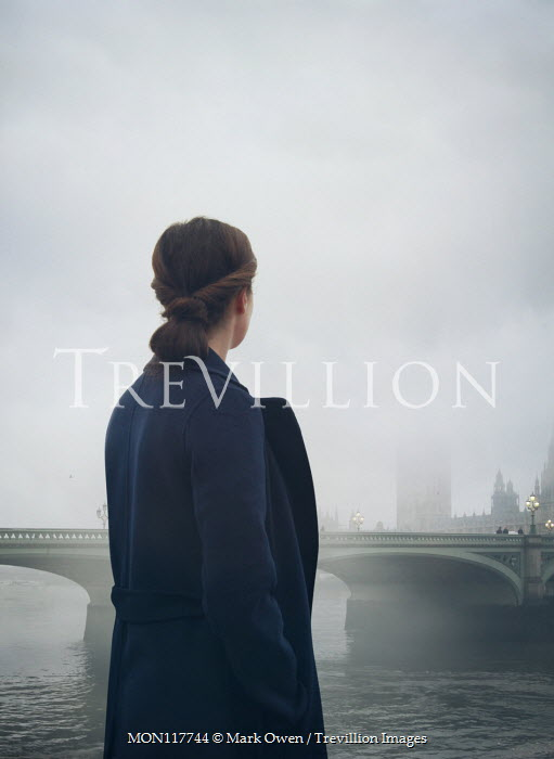 Mark Owen Young woman in coat by Westminster Bridge in London, England