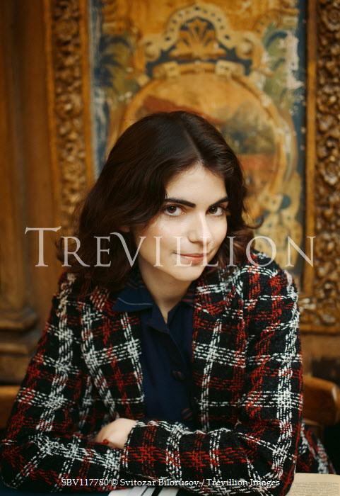 Svitozar Bilorusov Young woman in checked coat sitting at restaurant