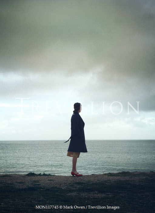 Mark Owen Young woman in coat by sea