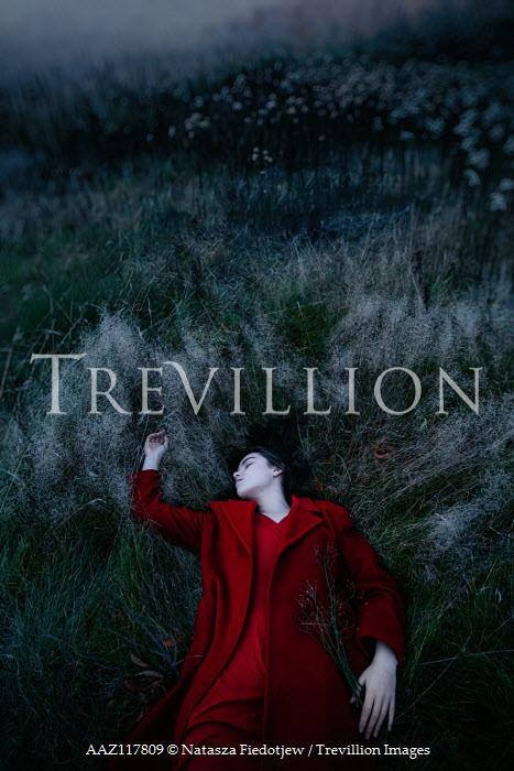 Natasza Fiedotjew Woman in red coat lying in field at dusk Women